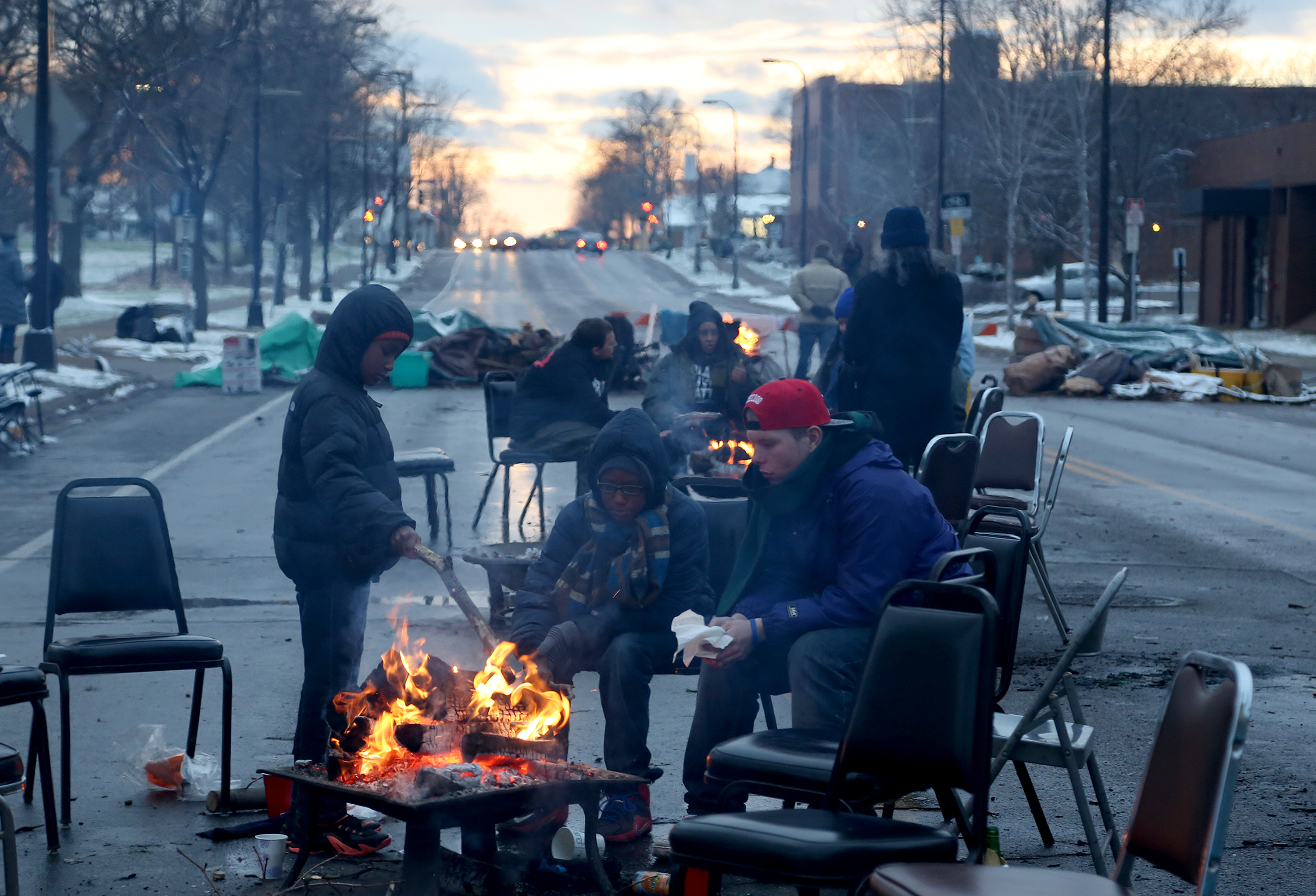 Community members and protesters warmed themselves by the fire during BlackGiving event in front of the Minneapolis Fourth Precinct. ] (KYNDELL HARKNESS/STAR TRIBUNE) kyndell.harkness@startribune.com BlackGiving event on Plymouth Ave in front of the Minneapolis Fourth Precinct in Minneapolis Min., Thursday November 26, 2015.
