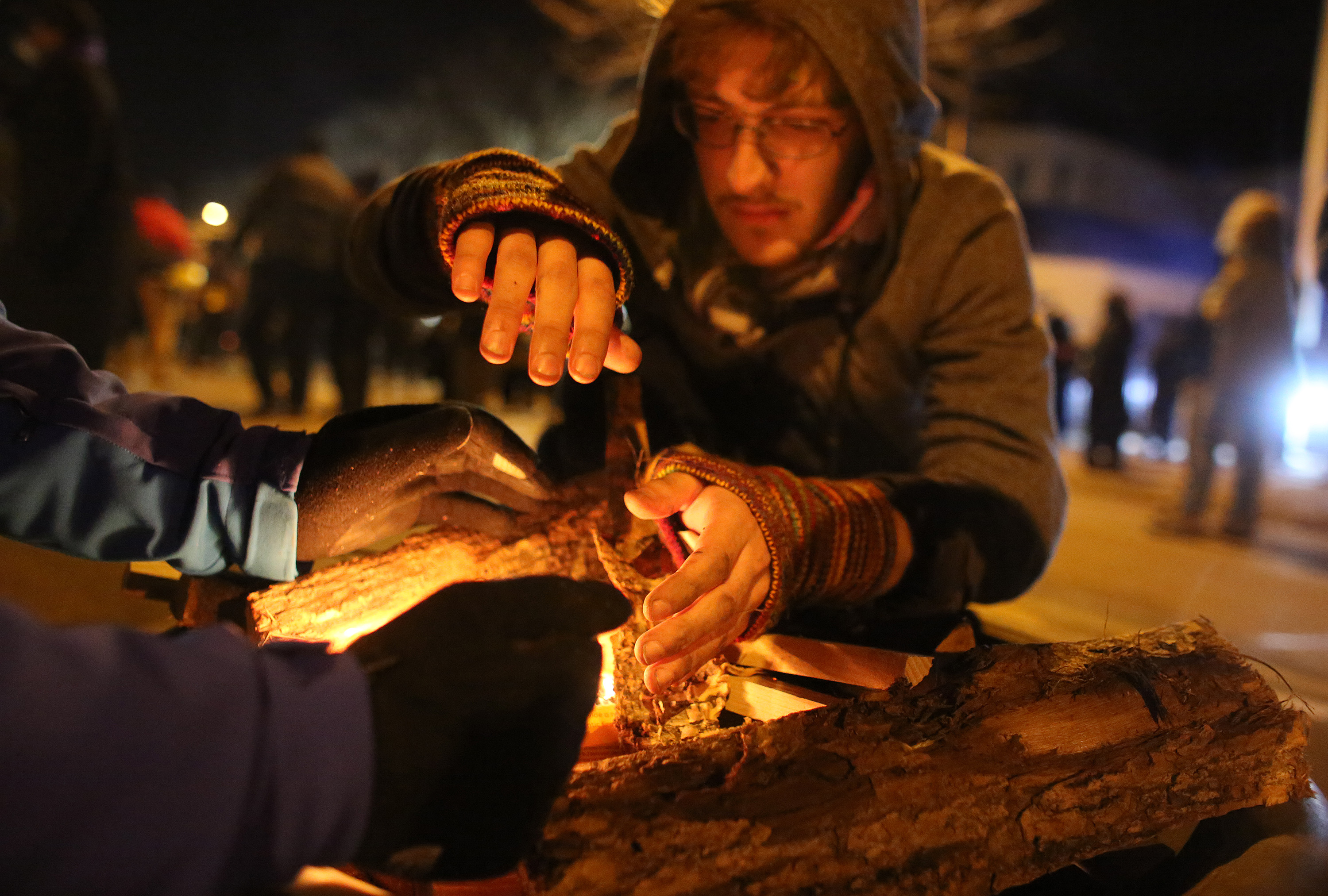 Andrew Bickford helped start a fire in one of the several fire pits on the five day of protesting in front of the Minneapolis Fourth Precinct. ] (KYNDELL HARKNESS/STAR TRIBUNE) kyndell.harkness@startribune.com Protesters in front of Minneapolis Fourth Precinct in Minneapolis Min., Thursday November 19, 2015.